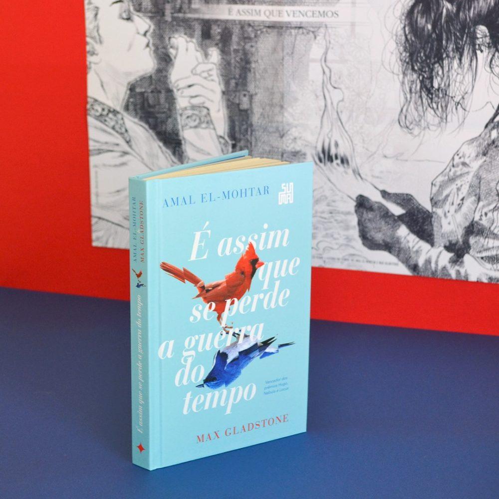 Capa do romance 'É assim que se perde a guerra do tempo' de Amal El-Mohtar e Max Gladstone, apoiada em um piso azul ao lado de uma parede vermelha com um pôster em preto e branco inspirado na obra, ilustrando ambas as personagens. A capa é azul clara, com dois pássaros opostos, um vermelho para cima, e um azul para baixo, ligados por suas patas. O vermelho olha para a direita enquanto o azul olha para a esquerda. Ambos os pássaros são segmentados por linhas invisíveis, deixando-os com um aspecto fora de sincronia. No topo, o nome de Amal El-Mohtar, em letras maiúsculas e azuis, com o selo da editora no canto direito. Na parte de baixo, o nome de Max Gladstone, em letras maiúsculas e vermelhas, com um anúncio diretamente acima dizendo 'Vencedor dos prêmios Hugo, Nebula e Locus' em letras azuis.