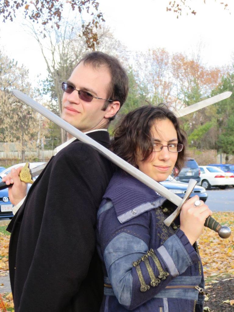 Foto dos autores de 'É assim que se perde a guerra do tempo'. Max Gladstone e Amal El-Mohtar, de costas um para o outro, em frente a um estacionamento, com espadas apoiadas nos ombros, olhando para a câmera, num dia ensolarado. Max, o mais alto, à esquerda, caucasiano, cabelos escuros e curtos, usa um terno escuro por cima de uma camisa branca, com óculos escuros e quadrados e um sorriso, segurando uma espada na mão direita e a apoiando no ombro direito. Amal, mais baixa, à direita, pele clara, usando um casaco azul escuro com detalhes em azul claro e rendas douradas, um óculos quadrado, segura uma espada de guarda prateada na mão direita, apoiando-a no seu ombro direito e tocando o ombro esquerdo de Max. Atrás deles, um estacionamento cheio de carros, com algumas árvores com poucas folhas ao fundo.