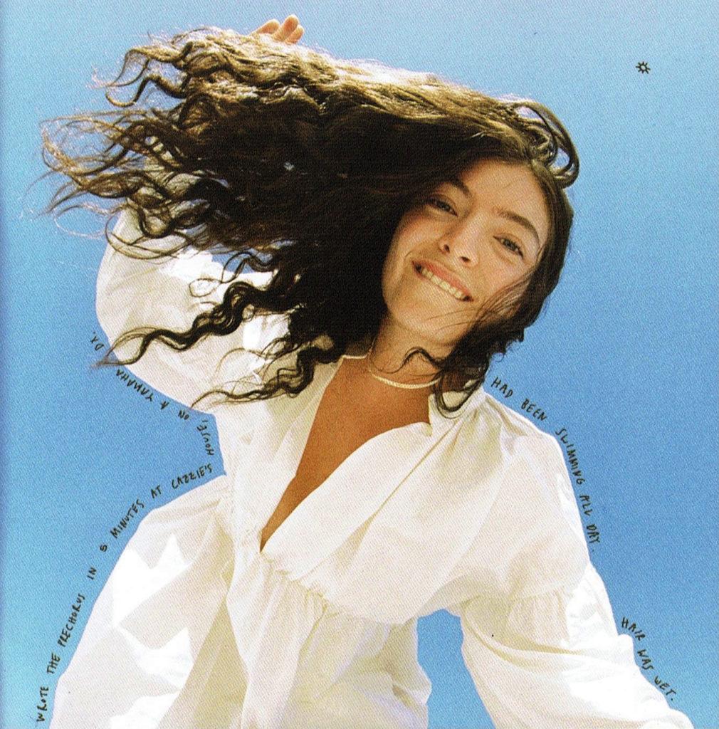 Fotografia quadrada. A câmera está no chão, e fotografa a cantora Lorde, uma mulher branca de cabelos ondulados, que olha de cima para a câmera. Ela está de cabelos soltos e veste uma camisa branca de decote. Acima dela, há um céu azul.