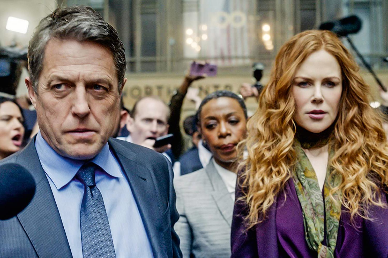 A imagem é uma cena da série The Undoing. Nela Hugh Grant, que interpreta Jonathan Fraser (à esquerda), e Nicole Kidman (à direita), que interpreta Grace Fraser, estão passando entre uma multidão de jornalistas, com um olhar preocupado. Jonathan é um homem branco, com cabelos grisalhos e olhos azuis, ele veste uma camisa, gravata e um terno em tons azuis. Grace é uma mulher branca, de cabelos ruivos e longos, ela veste um vestido e casaco roxos.