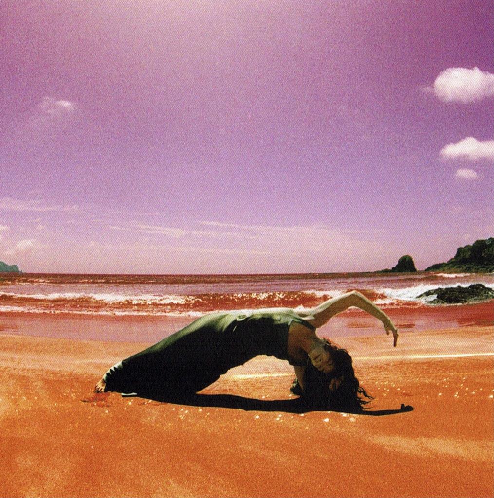Fotografia quadrada. Lorde está na areia da praia próxima ao mar, de costas para ele, fazendo uma pose em que toca os pés e um dos cotovelos no chão, e arqueia o resto do corpo, deitada. Seu outro braço está no ar, e seus cabelos tocam o chão. Ela veste um vestido longo verde musgo. Ao fundo dela, há o mar. O dia é ensolarado, e o céu foi colorido artificialmente para ficar roxo, e a areia para ficar laranja.