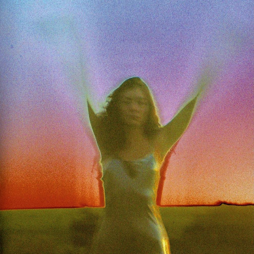 Fotografia quadrada. A câmera tirou uma fotografia tremida, mas mostra Lorde com os braços para cima, o rosto meio borrado. Ela usa um vestido prateado. O fundo é um céu que foi colorido artificialmente com um degradê que começa de cima para baixo, e vai de azul para roxo, para rosa, para vermelho, e termina num laranja avermelhado. A parte mais inferior da imagem, ainda ao fundo de Lorde, é uma faixa em verde-musgo.