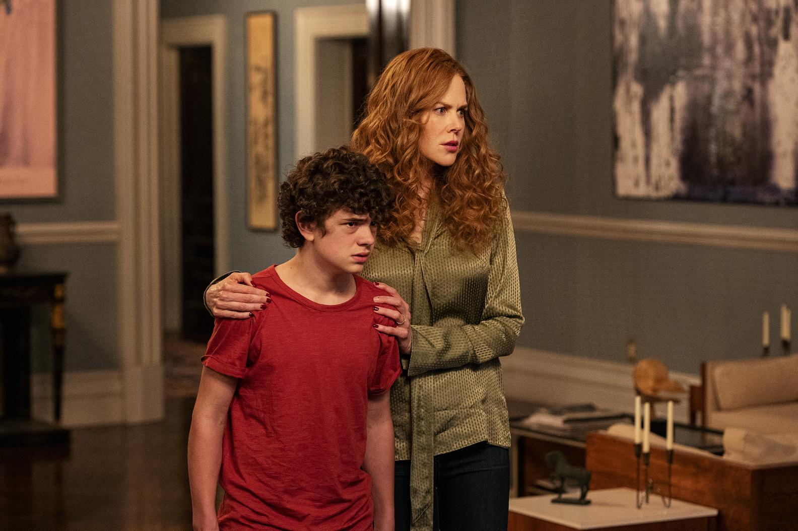 A imagem é uma cena da série The Undoing. Nela estão Nicole Kidman, que interpreta Grace Fraser e Noah Jupe, que interpreta Henry, na sala de sua casa. Grace é uma mulher branca, de cabelos ruivos e longos, ela veste uma blusa de mangas compridas em tom verde e uma calça preta; Grace está com as mãos segurando os ombros do filho. Henry é um menino branco, de cabelos castanhos escuros cacheados, ele veste uma camiseta vermelha.