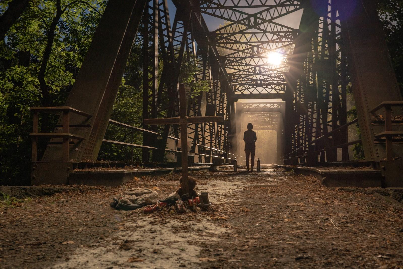 Cena do filme Um Lugar Silencioso - Parte II. É uma imagem retangular. No centro da imagem há uma cruz de madeira fincada no chão, na parte central direita há uma pessoa ao fundo, sua figura está nas sombras. A pessoa está andando em uma ponte de metal. O chão é de terra. Ao redor da ponte tem algumas árvores e acima há o brilho do sol.