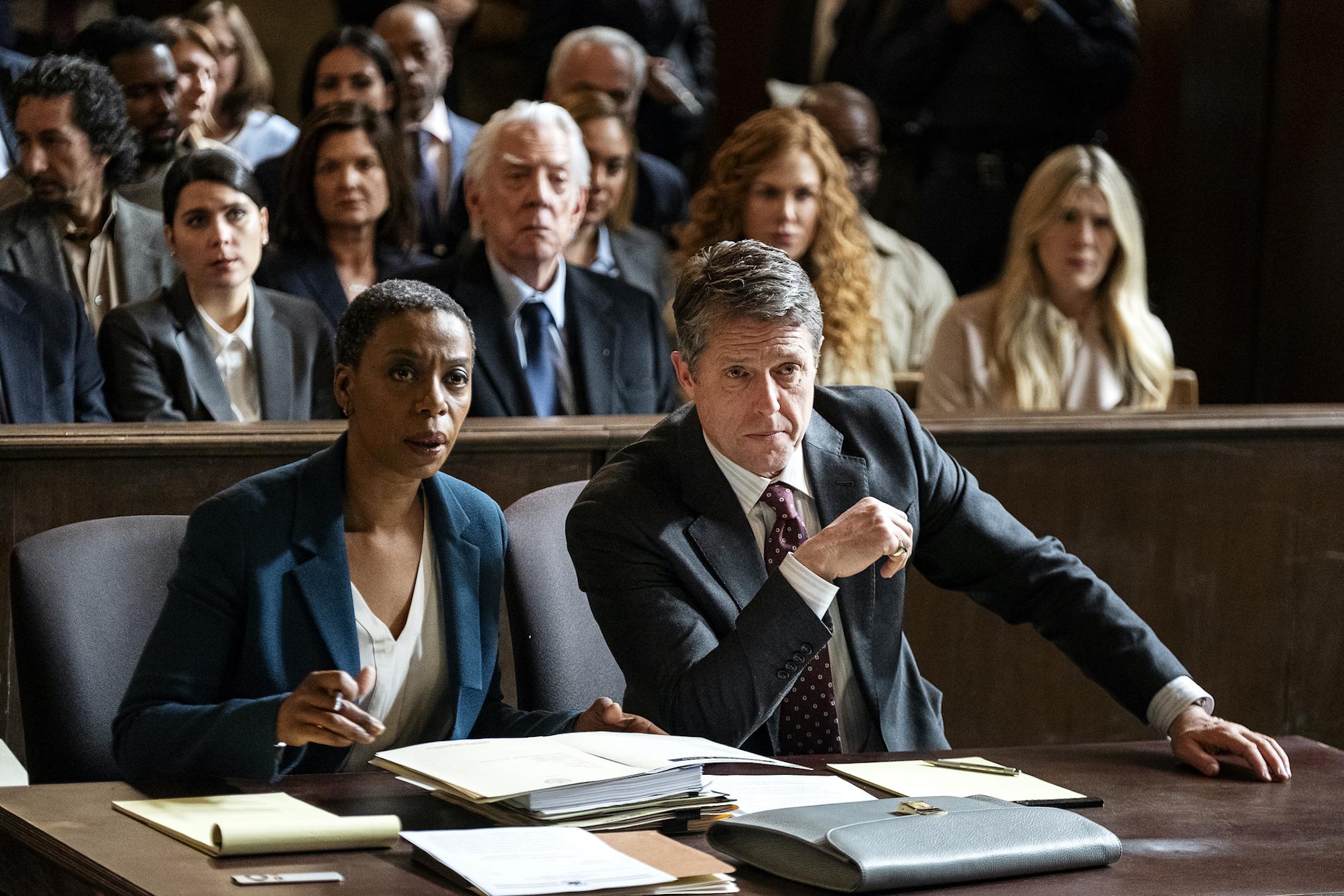 A imagem é uma cena da série The Undoing. Nela estão Hugh Grant, que interpreta Jonathan Fraser, e Noma Dumezweni, que interpreta Haley Fitzgerald, sentados à mesa em um tribunal. Jonathan é um homem branco, com cabelos grisalhos e olhos azuis, ele veste uma camisa branca, uma gravata vinho com bolinhas e um terno preto. Haley é uma mulher negra, com cabelo raspado, ela veste uma camisa branca e um terno azul marinho. Na mesa em que estão, há papéis e cadernos espalhados.
