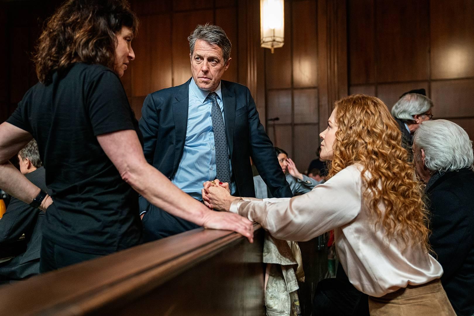 A imagem é uma cena da série The Undoing. Nela Hugh Grant, que interpreta Jonathan Fraser, e Nicole Kidman, que interpreta Grace Fraser, estão em um tribunal. Hugh está em frente à Nicole, separado por uma divisória. Ele é um homem branco, com cabelos grisalhos e olhos azuis, ele veste uma camisa, gravata e um terno em tons azuis. Nicole está com os braços apoiados na divisória. Ela é uma mulher branca, de cabelos ruivos e longos, ela veste uma camisa branca de mangas compridas. Ambos estão com o olhar direcionado para a diretora Susanne Bier, que está ao lado de Hugh. Ela é uma mulher branca, de cabelos castanhos escuros na altura dos ombros, e veste uma camiseta e calça pretas.