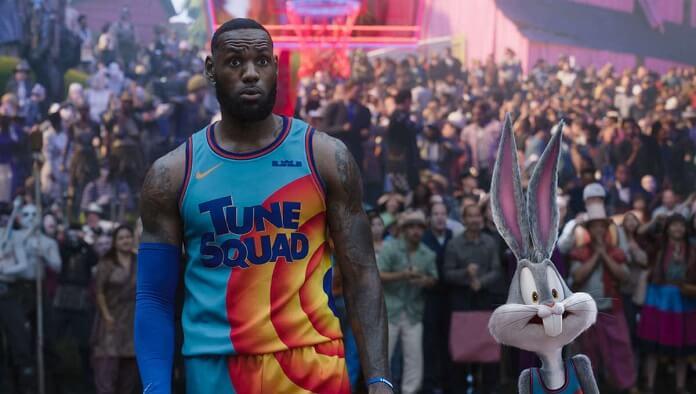 Cena do filme Space Jam 2, que mostra Lebron James e Pernalonga. Lebron é alto, negro e usa uniforme azul e laranja. Pernalonga é um coelho, animado, cinza e usa o mesmo uniforme. Ao fundo, vemos a torcida.