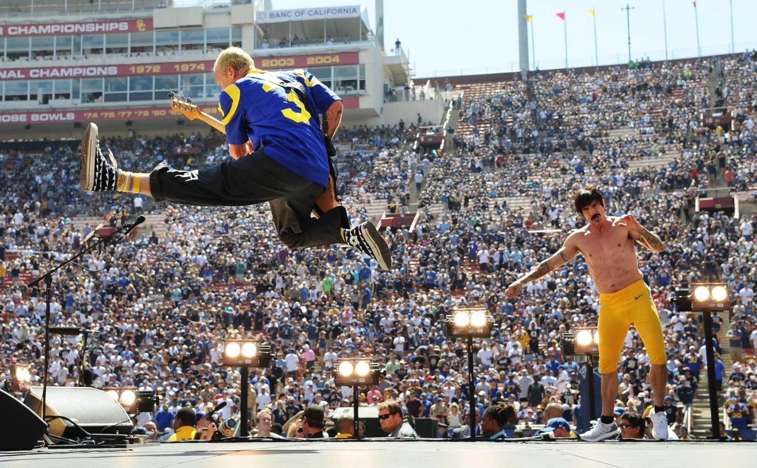Ao fundo tem a arquibancada lotada no jogo de futebol americano do time Los Angeles Rams. No palco está o baixista Flea e o vocalista Anthony Kiedis iluminados por holofotes. Na parte superior esquerda, o baixista tem cabelo platinado e raspado. O baixista é registrado com o baixo de costas com um pulo alto em movimento de chute para a frente. O baixista veste a camisa do time Los Angeles Rams na cor azul e com detalhes amarelos, calça preta e tênis preto. Na parte direita da imagem, está o vocalista com cabelo castanho e bigode. O vocalista está de frente sem camisa, de bermuda amarela e tênis branco.