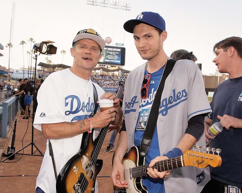 O baixista Flea e o guitarrista Josh Klinghoffer em um estádio de futebol americano. Flea tem o cabelo raspado em um tom turquesa, está de blusa branca com detalhes azuis, veste um boné branco, preto e amarelo. No corpo de Flea está pendurado um baixo preto e marrom. Flea está sorrindo e segurando um copo de café. Do seu lado direito está Josh Klinghoffer de camiseta azul com detalhes brancos e por cima uma camisa aberta cinza com detalhes azuis. Josh Klinghoffer está de boné azul com detalhes brancos e está segurando uma guitarra preta, marrom e branca.