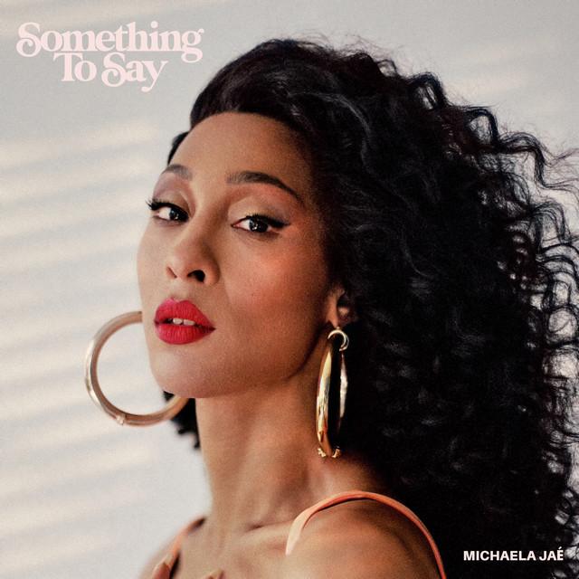 """Capa do single Something To Say. A imagem é o rosto da cantora Michaela Jaé, que encara a câmera, em fundo cinza. Ela é uma mulher negra com cabelos pretos cacheados esvoaçantes, usa brincos de argola dourados grandes, e batom vermelho. No canto superior esquerdo está escrito """"Something To Say"""" e no canto inferior direito """"Michaela Jaé"""""""