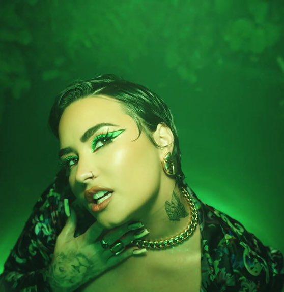 Imagem do clipe Melon Cake. No centro está Demi Lovato, pessoa não-binária branca de cabelos pretos curtos.. Elu usa uma camisa florida, corrente, brincos e anéis dourados, e uma maquiagem verde nos olhos. Sue expressão é sensual e olha para cima, enquanto sua mão direita está aberta e apoiada no pescoço. O fundo é de luz verde neon