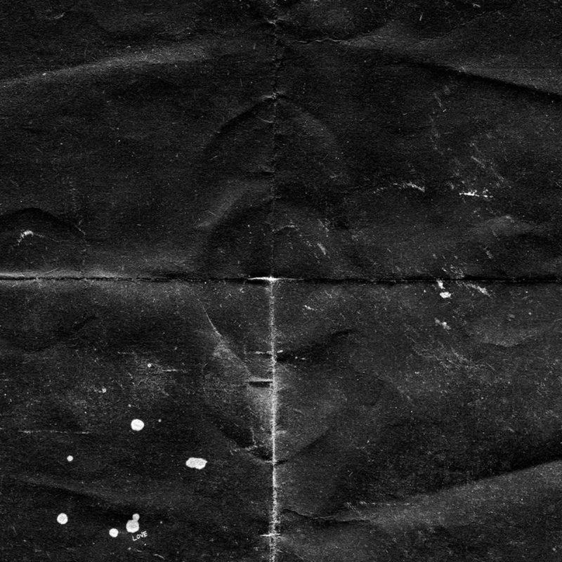 """Capa do álbum Wounded Rhymes (Anniversary Edition), de Lykke Li. Fotografia quadrada e abstrata. Não fica claro qual o objeto da imagem. Se assemelha a uma folha de papel dobrada em quatro partes simétricas. O papel é preto, amassado e gasto. Entre as dobras, destacam-se linhas brancas de desgaste da folha preta. A folha preta apresenta também marcas brancas desfiguradas, como respingos de tinta. Na parte inferior à esquerda, é possível ver a palavra """"LOVE"""" em branco, bem pequena, quase imperceptível."""
