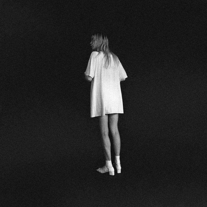 Capa do álbum Everything, de Bnny. Fotografia quadrada com filtro granulado em preto e branco. O fundo da imagem é todo preto. Ao centro está Jess Viscius, vocalista da banda, de pé e de costas. Ela é uma mulher branca, de cabelos claros e aproximadamente 25 anos. Ela veste uma camisa branca larga, meias brancas e sandálias brancas.