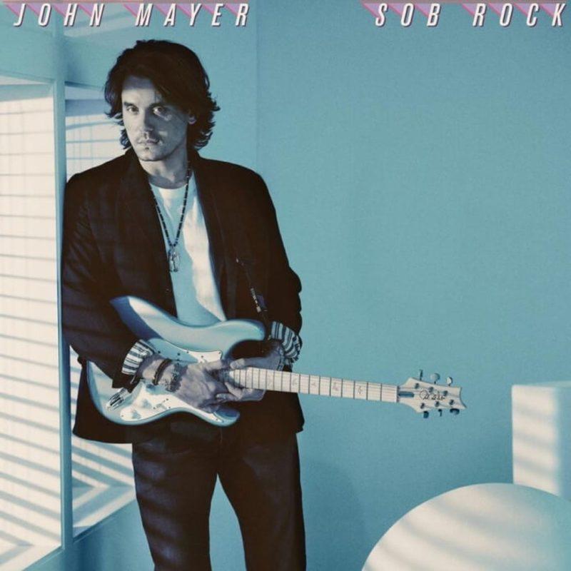 Capa do álbum Sob Rock, de John Mayer. A imagem é composta por uma fotografia que mostra artista, um homem branco, de cabelos castanhos lisos na altura dos ombros, dos joelhos para cima. John está no lado esquerdo da imagem, escorando seu ombro direito numa janela enquanto segura uma guitarra branca e preta. John veste uma camisa branca, blazer preto e uma calça jeans escura, e usa pulseiras nas mãos e um colar longo no pescoço. Ele sorri suavemente e seu rosto está levemente inclinado para o lado esquerdo da imagem, mas ele olha para a câmera. Atrás dele, existe uma parede clara, e a imagem é tingida em tons de azul. No canto superior esquerdo, está escrito o nome do artista em fonte simples em caixa alta na cor branca e com sombra rosa. Na mesma estilização, no canto superior direito, está escrito o nome do álbum.