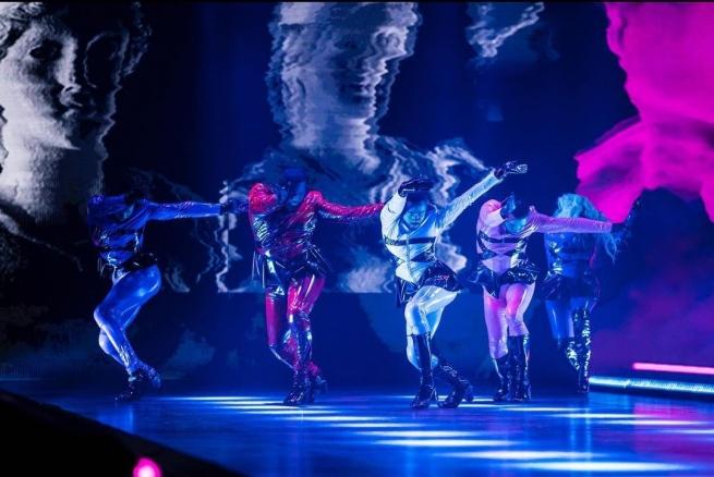Cena de Legendary. Em uma das apresentações, cinco pessoas estão usando roupas de látex, cada uma de uma cor, com detalhes em preto. Todas dançam com as pernas cruzadas e as mãos esticadas para frente. O fundo possui fotos de estátuas.