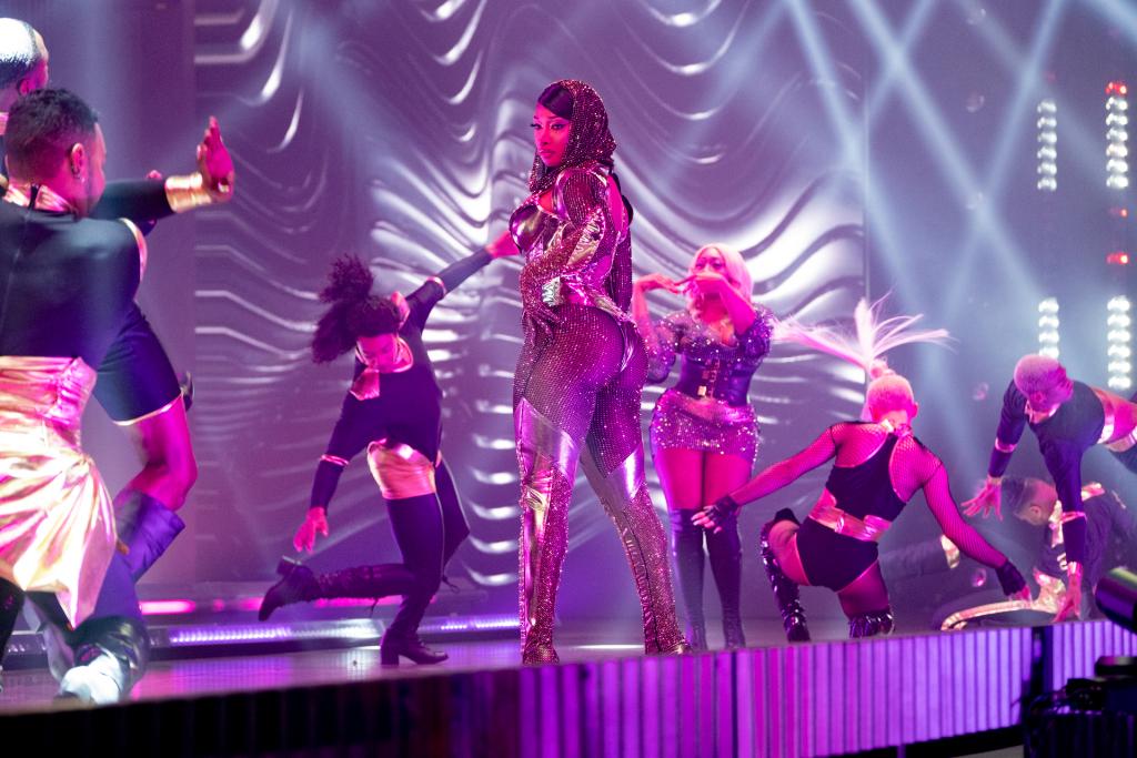 Cena de Legendary. No centro está Megan Thee Stallion, mulher negra de cabelo preto vestindo roupa preta transparente com detalhes em dourado. Ela está de pé, olhando para o lado. Ao seu redor outras pessoas dançam com roupas nas mesmas cores. O fundo e o palco são roxos.