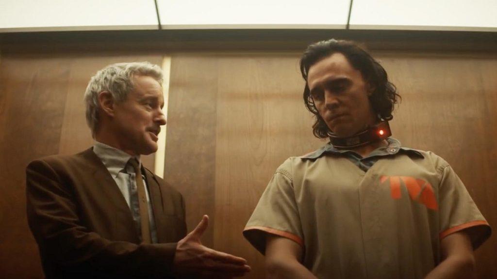 Cena da primeira temporada de Loki. Mobius (Owen Wilson) estende a mão para Loki (Tom Hiddleston), enquanto os dois estão num elevador. Mobius, caucasiano, cabelos curtíssimos e grisalhos, usa um paletó futurista marrom com as abas afundadas para dentro por cima de uma camisa social com gravata, também marrom, e olha para o outro com expectativa enquanto estende a mão. Loki, caucasiano e cabelos escuros até os ombros, usa algemas, uma coleira com uma luz vermelha e um uniforme pastel de prisioneiro da AVT com detalhes em laranja e o logo da organização na parte esquerda do peito, e olha desconfiado para a mão que Mobius estende. O elevador em que eles estão tem painéis de madeira polida nas paredes e lâmpadas quadradas e brancas no teto.
