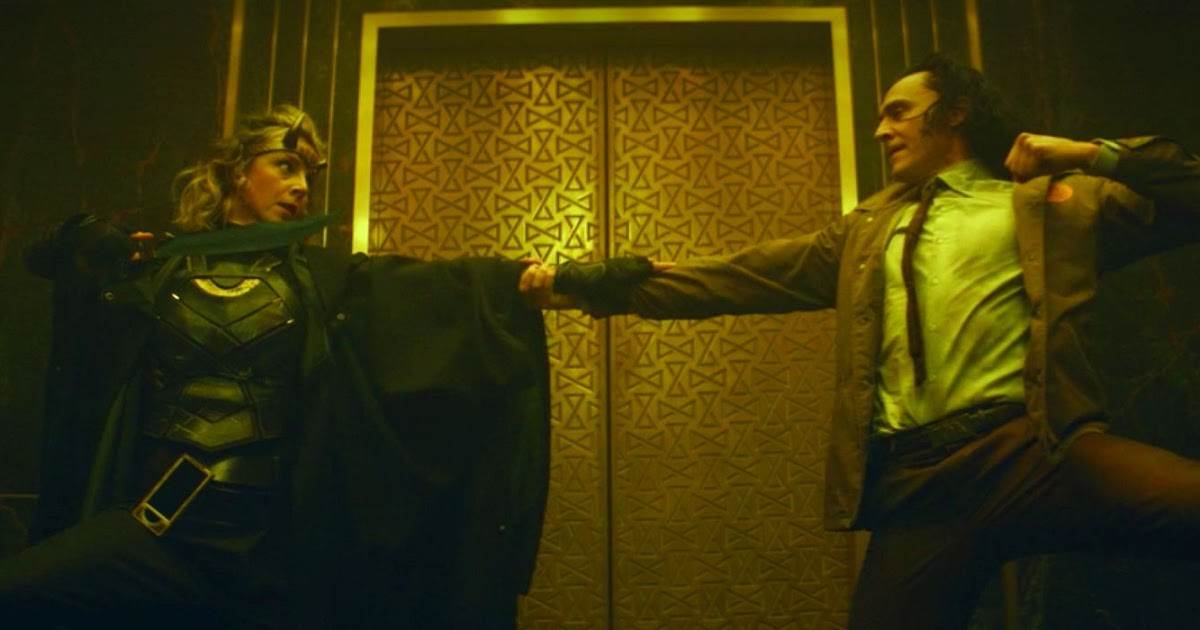 Cena da primeira temporada de Loki. Sylvie (Sophia Di Martino) e Loki (Tom Hiddleston) se enfrentam na frente do elevador que leva até os Guardiões do Tempo. Sylvie, caucasiana e de cabelos loiros e que vão até os ombros, usa um uniforme de couro de combate preto com poucos adereços dourados, por baixo de um sobretudo negro. Em sua testa, uma tiara de chifres dourados e curvos (o chifre esquerdo está partido). Ela segura uma espada com a mão direita, apontada para Loki, e com a esquerda segura o braço direito dele. Loki, caucasiano de cabelos negros até os ombros, usa uma jaqueta de tom pastel com o emblema alaranjado da AVT na parte esquerda, segurando o braço de Sylvie com uma mão enquanto a outra se fecha num punho em direção à ela. Atrás deles, o elevador da AVT com portas douradas e ilustrações em relevo em forma de ampulhetas. O elevador é cercado por mármore negro com linhas quadradas douradas adornando a porta. A cena é iluminada por uma cor amarela refletida nas portas do elevador.