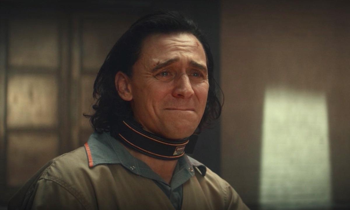 Cena da primeira temporada de Loki. Loki (Tom Hiddleston) está assistindo a todos os momentos de sua vida na sala de interrogatório da AVT. Loki, caucasiano de cabelos pretos até o ombro, usa o uniforme pastel de prisioneiro da AVT, vestindo uma camisa azul clara por baixo e usando uma coleira preta com bordas laranjas e um aviso de perigo. Sua cara está contorcida em um choro vulnerável e dolorido. Atrás e à esquerda dele, a porta da sala se estende do chão ao teto com uma cor acobreada. À direita,as paredes brancas da sala, iluminadas por uma única luz branca vinda do teto, que ilumina apenas um feixe reto para baixo.