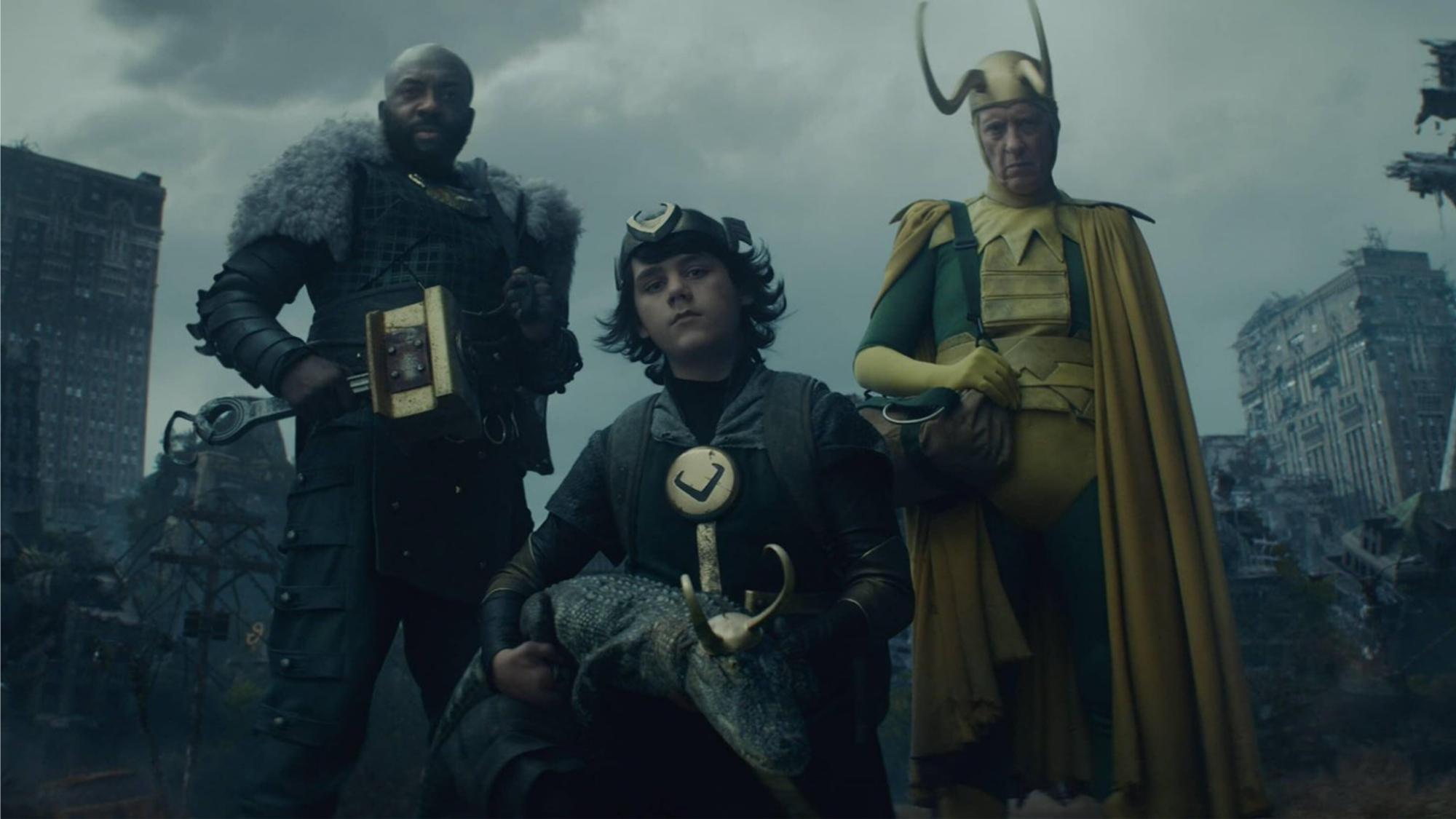 """Cena da primeira temporada de Loki. Algumas das outras variantes de Loki presas no Vazio, olhando para o Loki que acabou de acordar. Da direita para a esquerda: Loki Clássico (Richard E. Grant), caucasiano, idoso, usando um collant de cores verdes e amarelas vibrantes, uma capa e um par de chifres dourados longos e curvos em seu capacete, segurando uma bolsa com o braço direito. Agachado no centro da figura, Loki Criança (Jack Veal), caucasiano, cabelos longos e curvados, vestindo um uniforme verde escuro com adornos dourados com o símbolo dos dois chifres em """"V"""", uma tiara dourada com esse mesmo símbolo, as alças de uma mochila visíveis em seu ombro. Ele segura o Loki Jacaré, um jacaré com um pequeno elmo dourado com chifres curtos. Do lado dele, Loki Orgulhoso (Deobia Oparei), negro e careca, usando uma armadura de couro verde com um colar dourado, segurando um martelo rústico na mão direita. Atrás deles, as ruínas de uma grande cidade, cobertas por um céu cinza."""