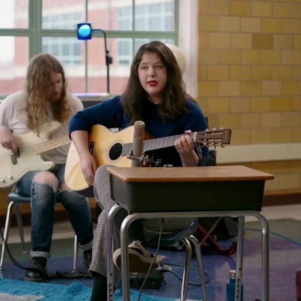 Foto da cantora Lucy Dacus em sua performance no Tiny Desk Concerts. Ela é branca, tem cabelos pretos e segura um violão. O cenário é uma sala de aula e ela está sentada à cadeira e à mesa escolar. Ao fundo, vemos alguém tocando violão também. Está de dia e o microfone está em cima da mesa, na frente de Lucy.