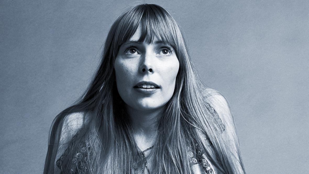Foto em preto e branco de Joni Mitchell olhando para cima com cabelos soltos.