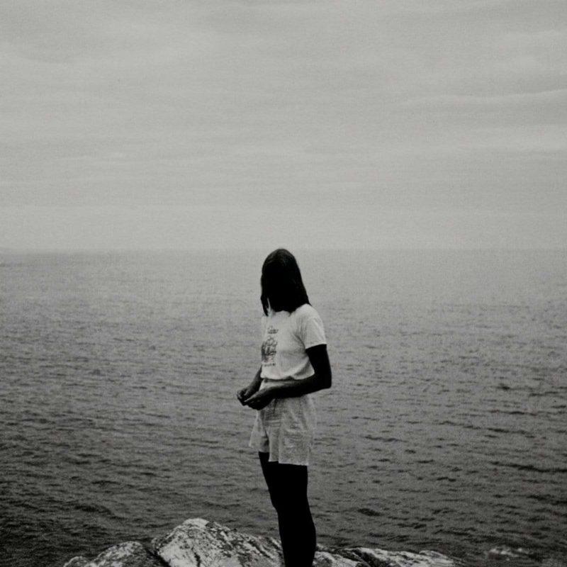 Capa do álbum Luminol, de Midwife. A imagem é composta unicamente por uma fotografia em preto e branco de uma jovem de pé numa pedra, de costas para um oceano calmo. A mulher está ao centro, virada para o lado esquerdo, e encara a câmera, mas seu rosto não é visível pelo contraste da imagem. Ela tem os cabelos lisos caindo sob o ombro e colocados atrás do corpo, veste um shorts de moletom de cintura alta e uma camiseta com uma estampa ao centro e segura as mãos juntas na frente do quadril. Parte das pedras onde ela está posicionada aparecem na linha inferior da imagem, e ao fundo, o mar se estende até se encontrar com o céu.