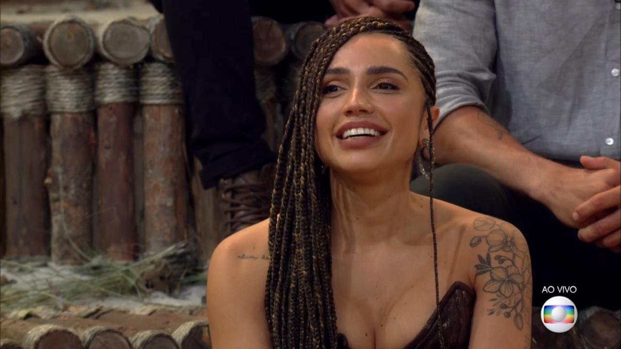 Cena do reality No Limite. Paula Amorim, vencedora da 5ª edição, está sentada no estúdio do programa no último episódio. Ela é uma mulher branca bronzeada e usa tranças no cabelo. Ela usa um vestido que mostra os ombros e possui um decote. Ela está sorrindo.