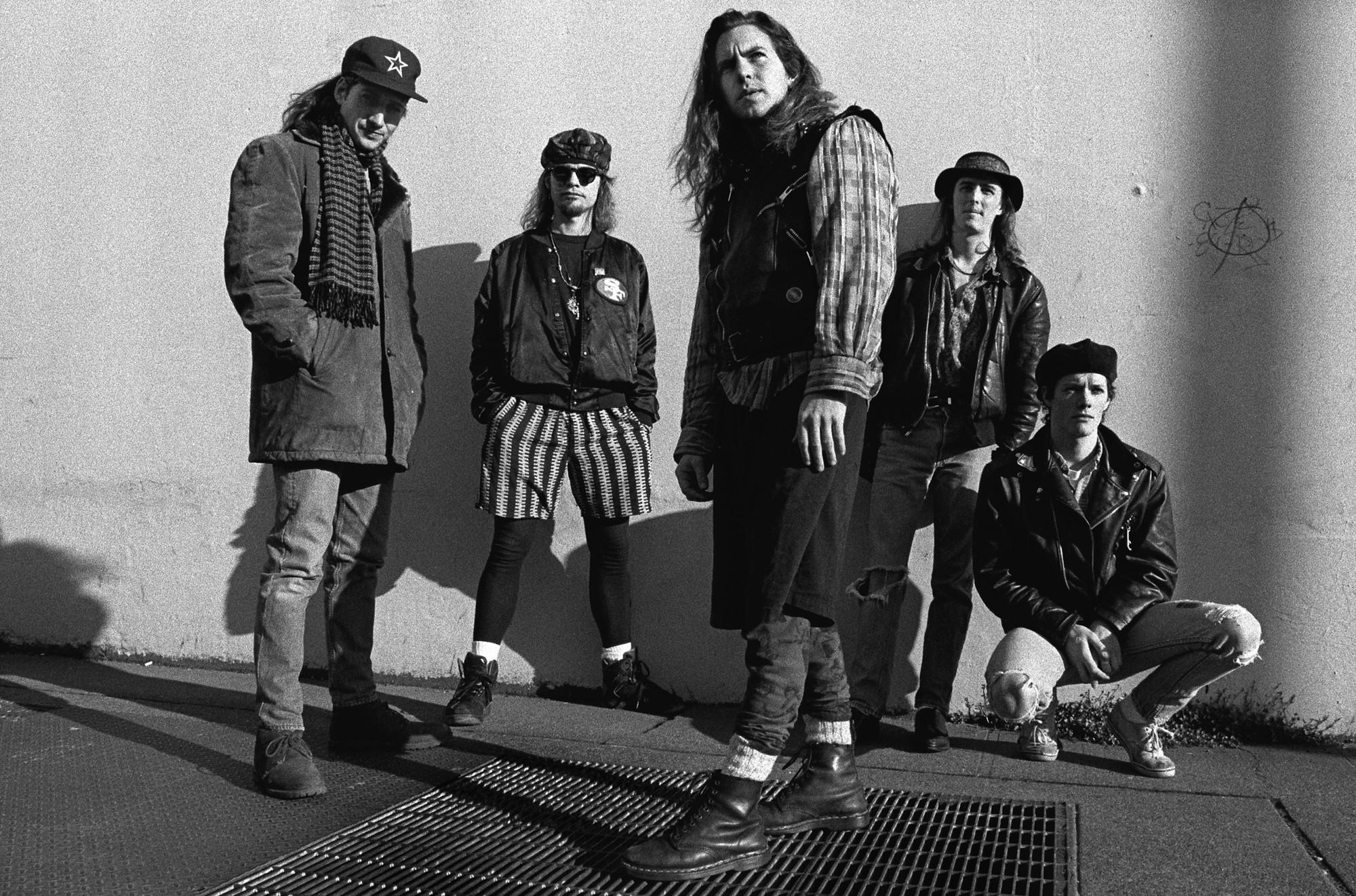 Foto dos integrantes da banda Pearl Jam. Os cinco integrantes são homens brancos, e, com exceção de Dave Krusen, todos possuem cabelos longos, abaixo do ombro. Na foto, em preto-e-branco, Stone Gassard veste um sobretudo, cachecol e um boné com uma estrela desenhada no meio. Jeff Ament veste coturno, meia-calça preta, shorts listrado preto-e-branco, jaqueta de couro preta e óculos escuros. Eddie Vedder usa coturno preto, camisa xadrez e um colete preto sobre a camisa, ele está à frente dos demais integrantes, parado em forma lateral olhando para o horizonte. Mike McCready está encostado na parede; ele veste chapéu, jaqueta de couro preta e calça jeans rasgada. Dave Krusen está agachado, usando uma boina preta, calça jeans clara rasgada e um tênis branco.