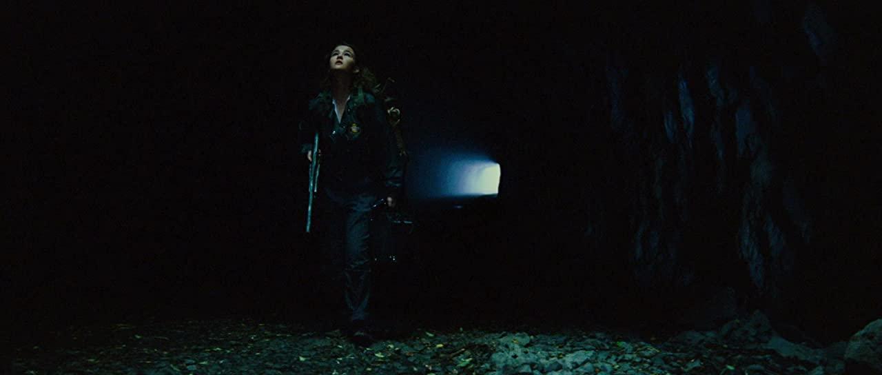 Cena do filme Um Lugar Silencioso - Parte II. A imagem é um túnel cavernoso com a personagem Regan Abbott, Millicent Simmonds, caminhando pelo centro. Regan é uma adolescente branca e está olhando para cima de onde uma luz a ilumina; ela está de jaqueta e calça jeans escuras, segura uma espingarda em uma mão e na outra um amplificador. Ao fundo há uma luz azul no final do túnel, e parte do chão à frente de Regan está coberto de folhas. A imagem tem pouquíssima iluminação