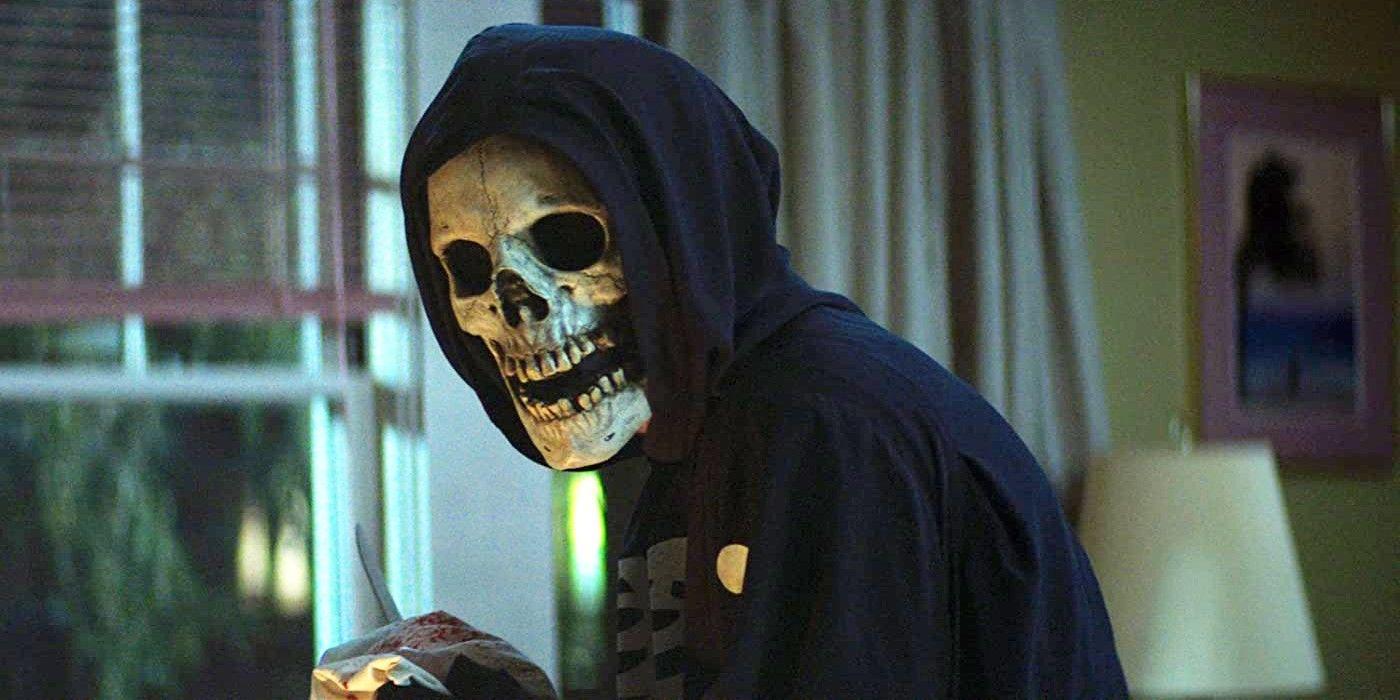 Cena do filme Rua do Medo: 1994 - Parte 1. É noite e uma figura encapuzada usando uma máscara de caveira olha para a câmera. Ela está dentro de uma casa, segurando um tecido ensanguentado com as mãos. Atrás dela, à esquerda, uma janela aberta com algumas árvores de fora. Do lado direito, uma cortina bege aberta, um abajur branco, uma parede amarela e um quadro pendurado nela.