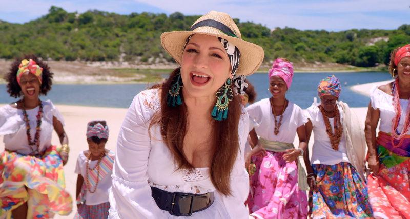 Cena de Sangue Iorubá. Ao centro temos Gloria Estefan. Uma mulher latina, de cabelos lisos, longos e avermelhados. Ela usa vestido branco e chapéu panamá com lenço azul e branco. Atrás dela vemos cincos mulheres negras com vestes brancas. Ao fundo vemos um lago de água cristalina, areia e árvores atrás.
