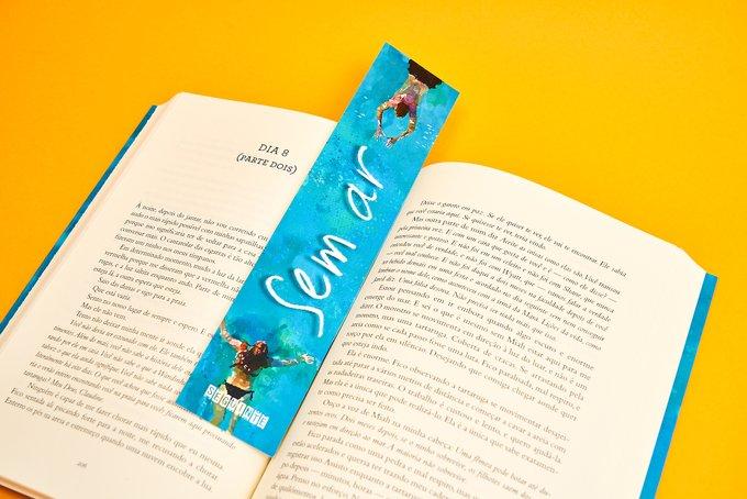 Foto do livro Sem Ar aberto. Entre as páginas está um marca pagina do livro que tem o desenho de um casal nadando em direção um do outro, com o fundo azul remetendo a água e o nome do livro no centro, de branco. O fundo da foto é amarelo.