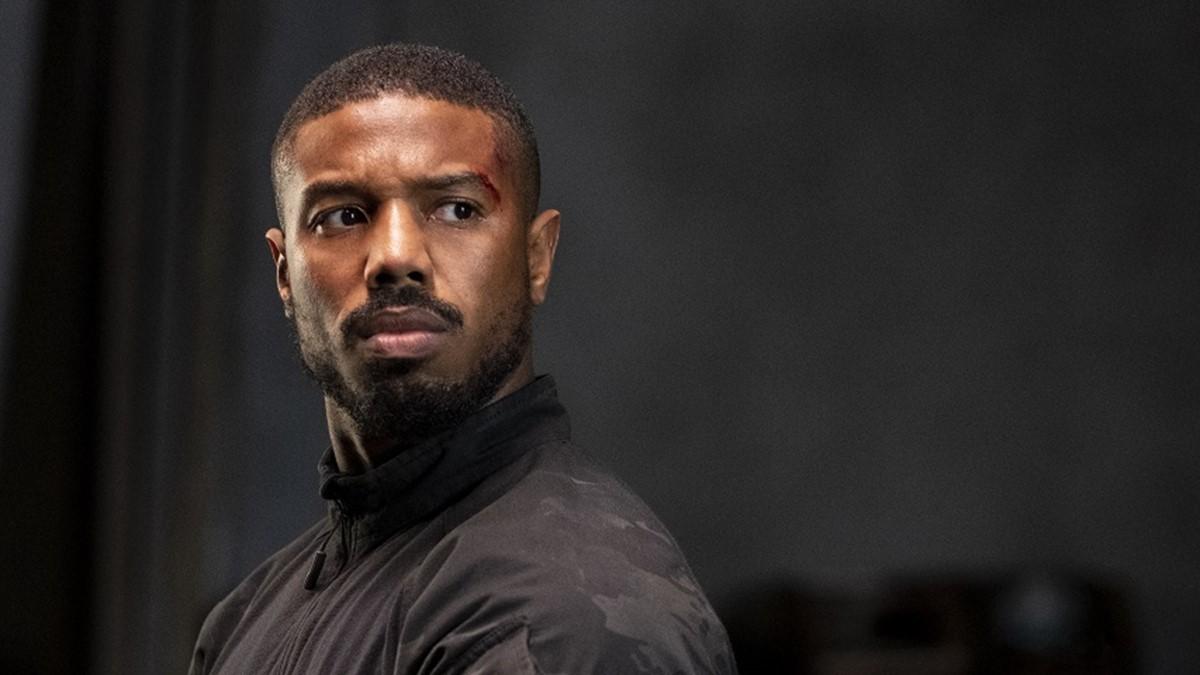 Cena do filme Sem Remorso exibe um homem negro que está olhando para o lado. Ele tem cabeça raspada e usa uma blusa preta, camuflada e de gola alta. Ao fundo, vemos uma parede preta.