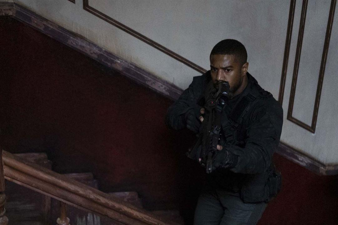 Cena do filme Sem Remorso exibe um homem negro, armado e parado num degrau de uma escada desgastada. Ele tem cabeça raspada, tem um olhar desconfiado e veste somente roupas pretas.