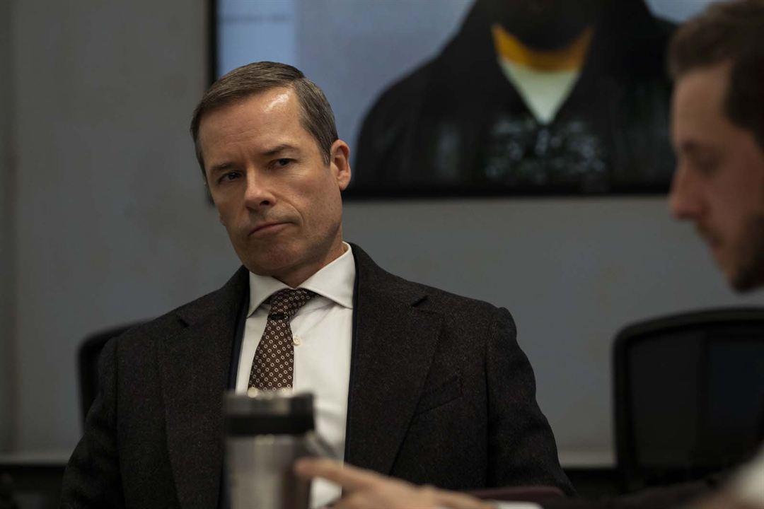 Cena do filme Sem Remorso exibe um homem branco que usa traje social. Ele tem o cabelo curto, em estilo militar, e está sentado em uma cadeira atrás de uma mesa. Ele olha para um homem no canto direito, que aparece borrado.