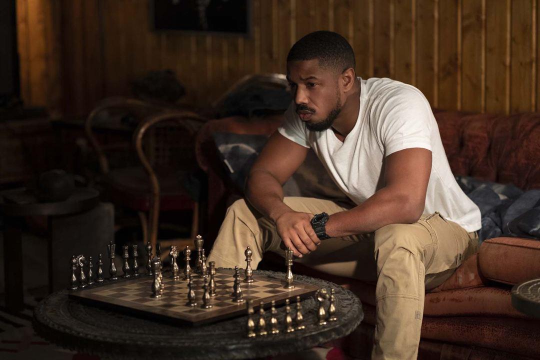 Cena do filme Sem Remorso exibe um homem negro, sentado em um sofá com um tabuleiro de xadrez em frente à ele, em cima de uma mesinha. Ele está usando uma camiseta branca, calça bege e um relógio no pulso esquerdo. Olha para a frente em vez de olhar para o tabuleiro.