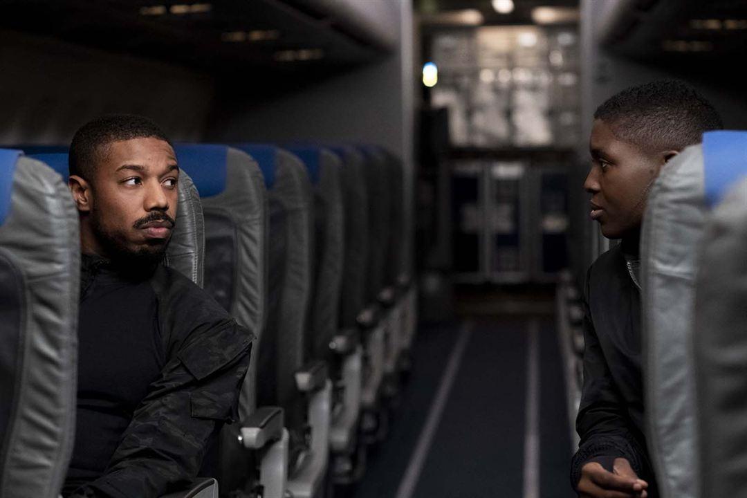 Cena do filme Sem Remorso exibe um corredor de um avião. Um homem negro está sentado no assento à esquerda e olha para uma mulher, também negra, à direita. Ambos têm cabeça raspada e usam roupas pretas.