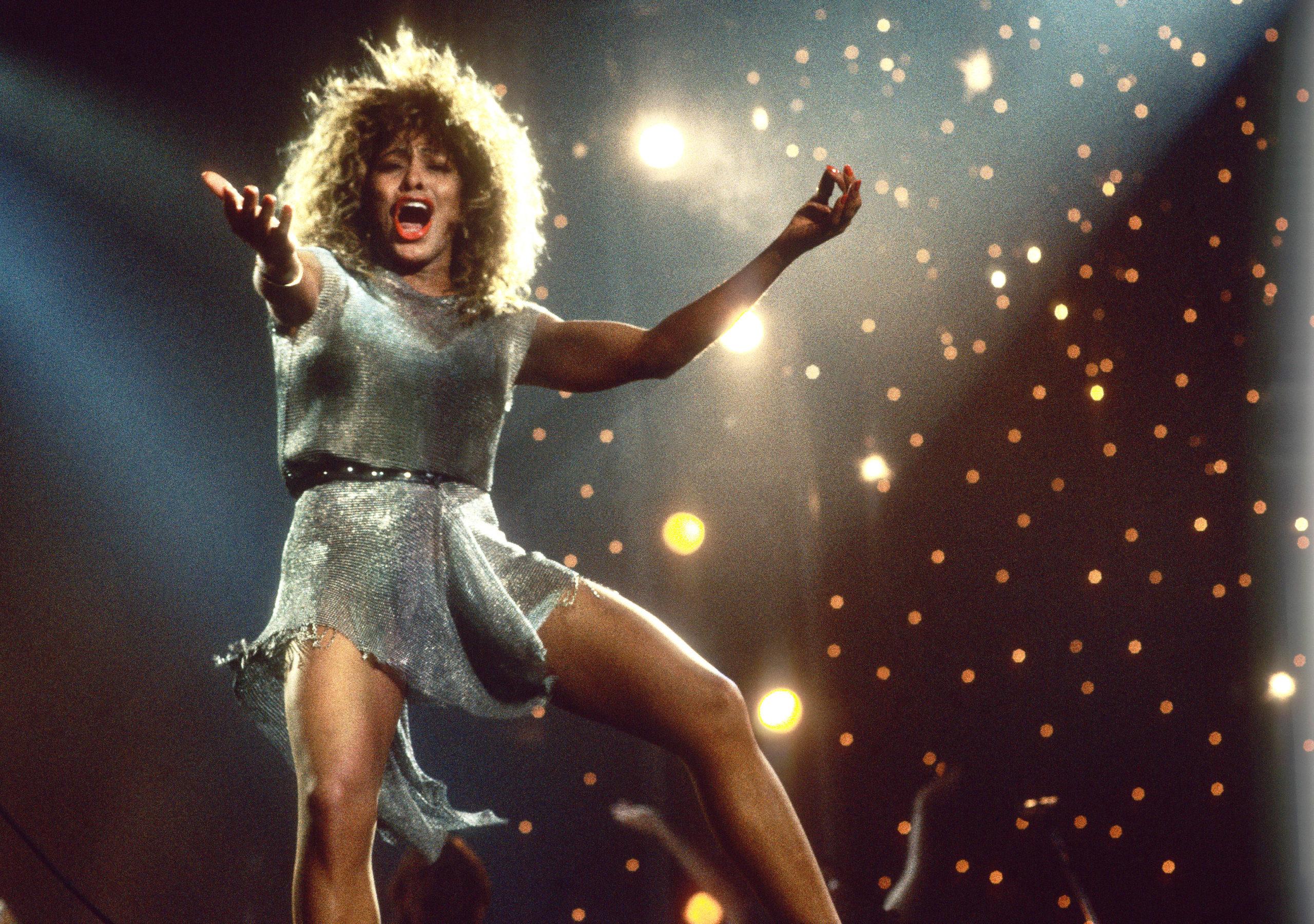 Cena do filme Tina. A imagem mostra Tina Turner no palco, fotografada dos joelhos para cima, cantando, com os braços estendidos, na frente de um fundo de luzes redondas amarelas. Tina é uma mulher negra, de cabelos cacheados volumosos loiros, e usa um vestido curto prateado com um cinto de spikes preto na cintura. Ela também usa batom vermelho.