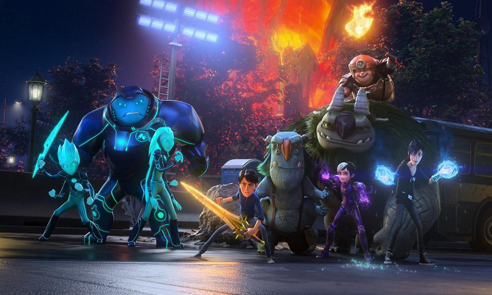 Cena do filme Trollhunters: A ascensão dos titãs. É noite e os heróis, finalmente reunidos, se preparam para enfrentar sua maior ameaça. Da direita para a esquerda, os alienígenas: Krel (Diego Luna), Vex (Nick Offerman), e Aja (Tatiana Maslany). Todos eles tem pele azul e usam armaduras azul-escuras. Krel e Aja possuem dois pares de braços e Vex é maior que eles. Krel segura uma espada futurista azul brilhante e Aja segura um dispositivo semicircular. No centro da imagem, Jim (Emile Hirsch), um humano, caucasiano, de jeans e blusa azul, segura Excalibur, uma espada dourada. À direita de Jim, os trolls: Blinky (Kelsey Grammer) e Aaarrrgghh!!! (Fred Tatasciore). Ambos tem a pele de pedra, mas Blinky é azul e Aaarrrgghh!!! é cinza. Blinky é um pouco maior que Jim e tem três pares de olhos, mas Aaarrrgghh!!! é um pouco maior que Vex e possui pelo verde nas costas. Em cima de Aaarrrgghh!!!, Toby (Charlie Saxton), um humano caucasiano pequeno usando uma armadura de bronze com uma lanterna no capacete e segurando um martelo flamejante. Na frente deles, Claire (Lexi Medrano), uma humana latina com uma armadura púrpura com luz mágica nas duas mãos. Do lado direito dela, Douxie (Colin O'Donoghue), um mago caucasiano de cabelo preto usando um moletom preto e com mágica azul saindo das mãos. Atrás deles há uma van estacionada, e atrás dela, uma floresta em chamas. Eles são iluminados pela luz de um holofote atrás deles.