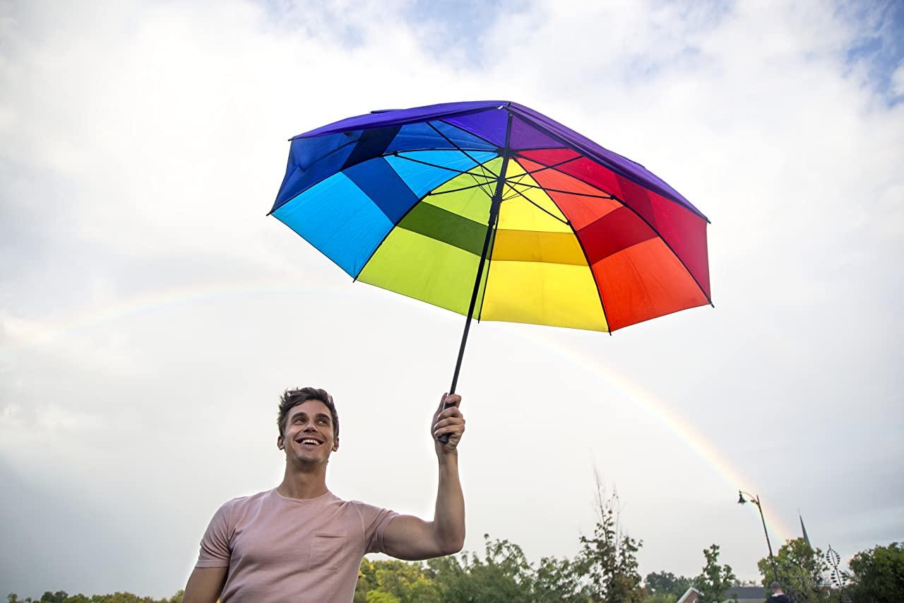 Cena da série Queer Eye. Na imagem Antoni está ao ar livre segurando um guarda-chuva de arco íris nas cores azul, verde, amarelo, vermelho, pink, roxo e azul turquesa. Ao fundo o céu está nublado e tem um arco-íris. Antoni é um homem branco de cabelos castanhos de franja arrepiada, ele usa uma camiseta rosa bebê e está olhando para o céu sorrindo.