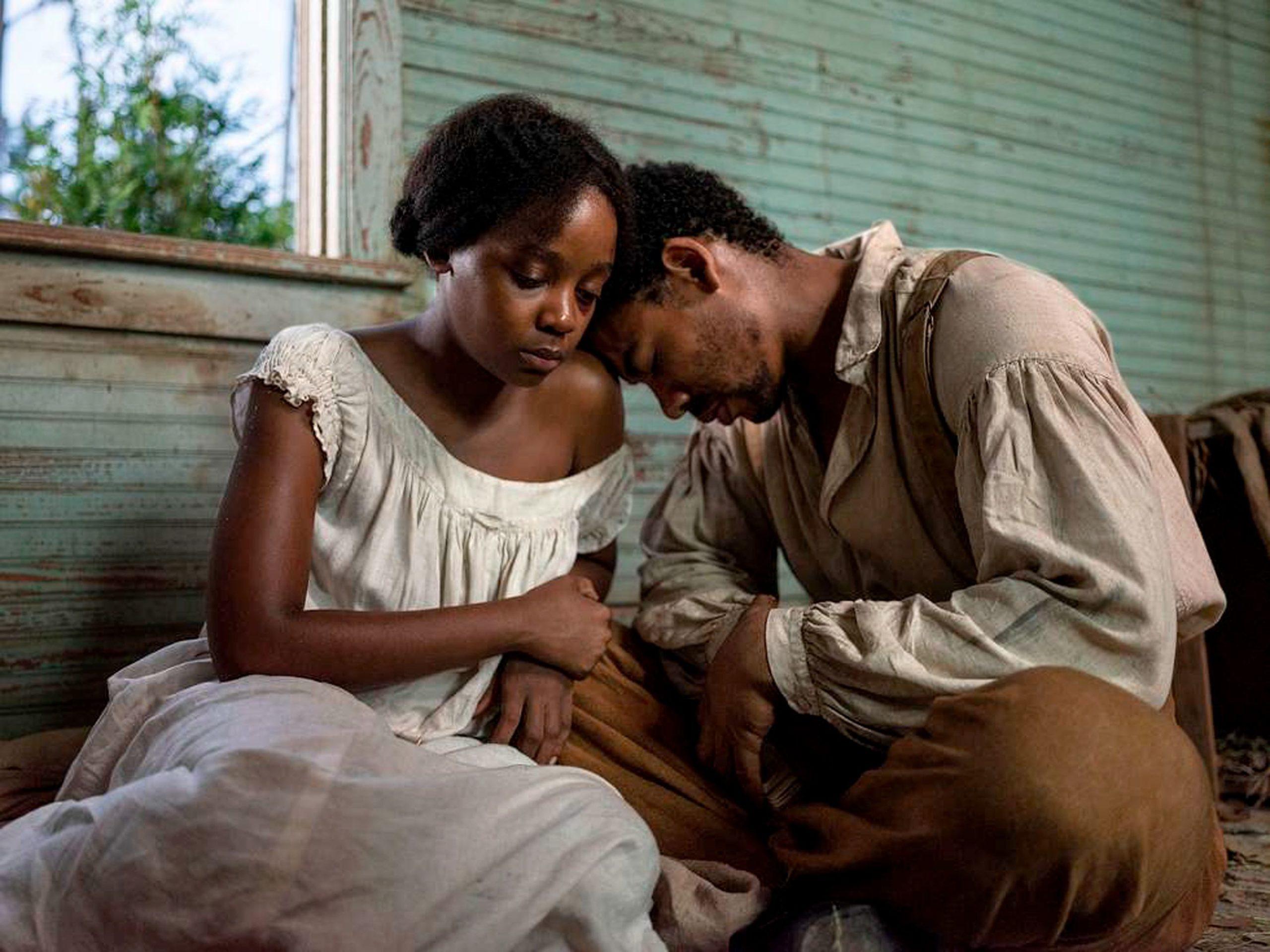 Cena da minissérie The Underground Railroad. A cena mostra dois jovens negros agachados e encostados um no outro. Cora é uma mulher, de cabelo preso num coque e Caesar é um homem de olhos claros, barba e cabelos pretos e veste roupas marrons.