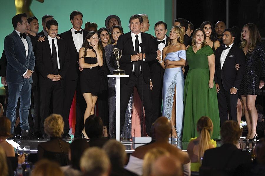 Foto da equipe de Ted Lasso. Em cima do palco estão 24 pessoas amontoadas. A maior parte olha para o homem que está no centro. Ele é branco e usa terno preto por cima de uma camisa branca. Na sua frente está um microfone onde o homem faz seu discurso e uma mesa branca onde o prêmio está apoiado.