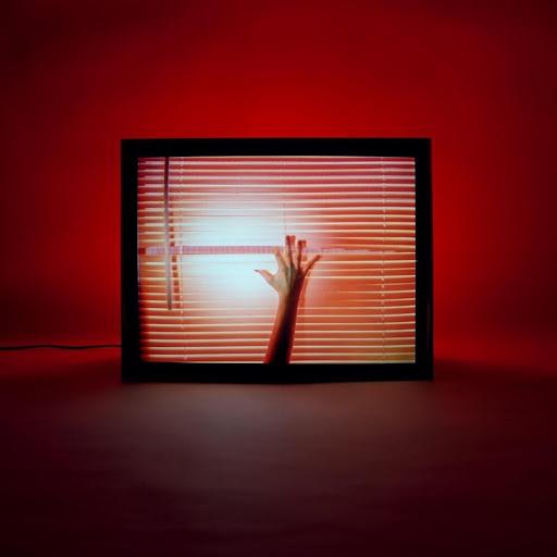 Capa do álbum Screen Violence, da banda CHVRCHES. Uma televisão em uma sala vermelha, de frente. Na tela, uma persiana fechada. Um braço se estende da parte inferior e, com o indicador da mão direita, abre uma fresta na persiana, revelando estática. Fora da televisão, há um fio preto se estendendo do canto esquerdo da televisão e indo para a borda esquerda da capa. Atrás da televisão há uma luz acesa, iluminando a parede vermelha.