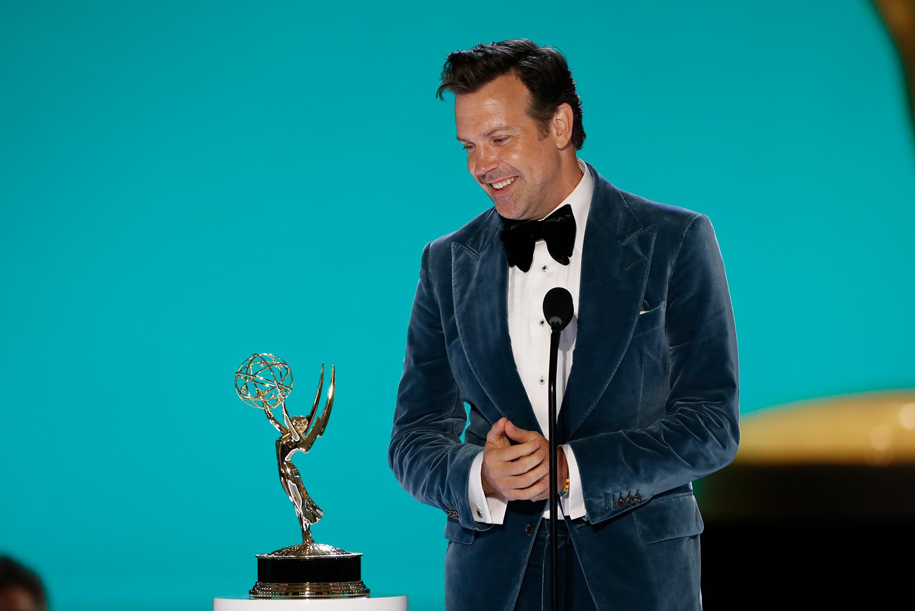 Foto de Jason Sudeikis. O homem branco usa terno azul por cima de uma blusa branca. Ele sorri olhando para o premio ao seu lado, segurando as maõs ma frente. De pé ao lado de um microfone, ela segura uma estatueta do Emmy, que é dourada e tem base preta. O fundo tem uma tela azul e um grande prêmio que está embaçado para ver.