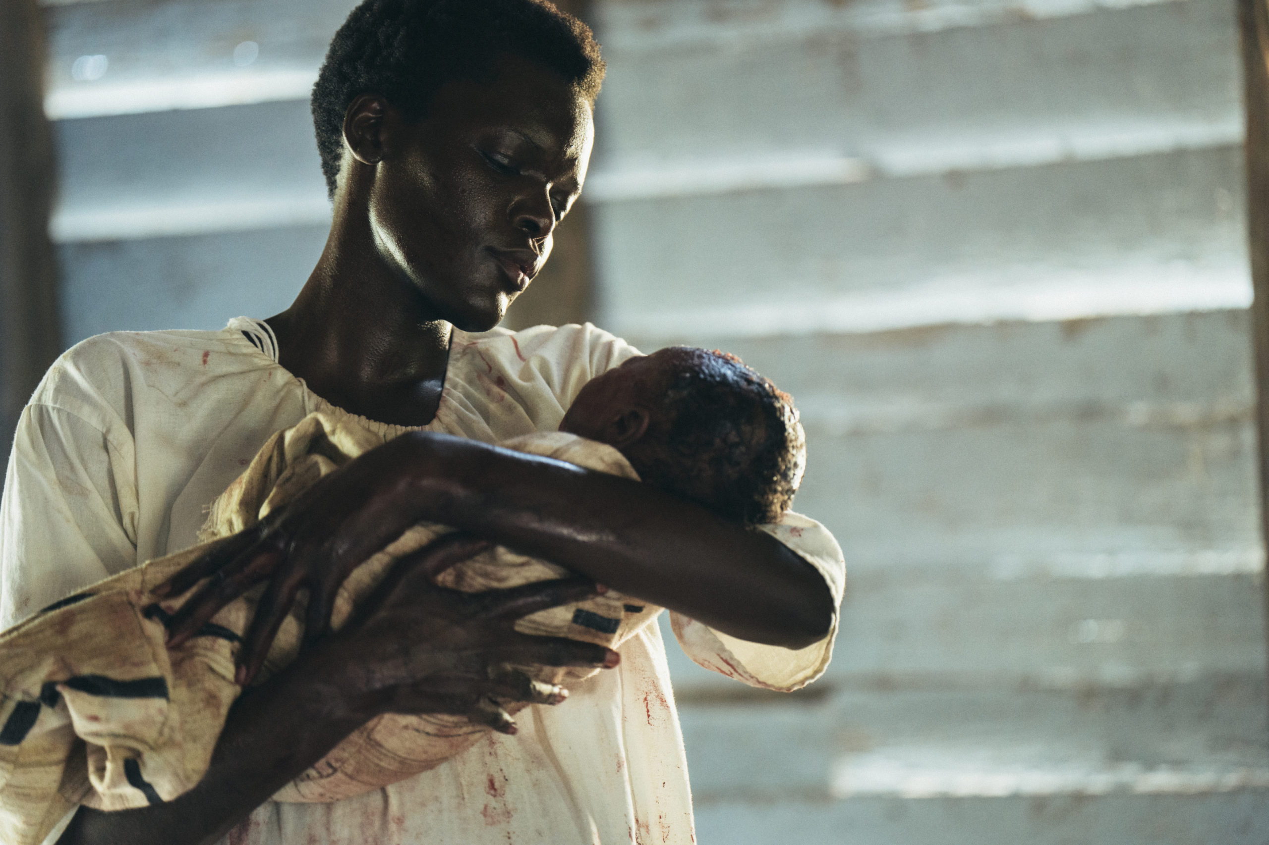 Cena da série The Underground Railroad. A cena mostra Mabel, uma mulher negra retinta adulta, vestido uma camisola branca, segurando um bebê negro no colo.