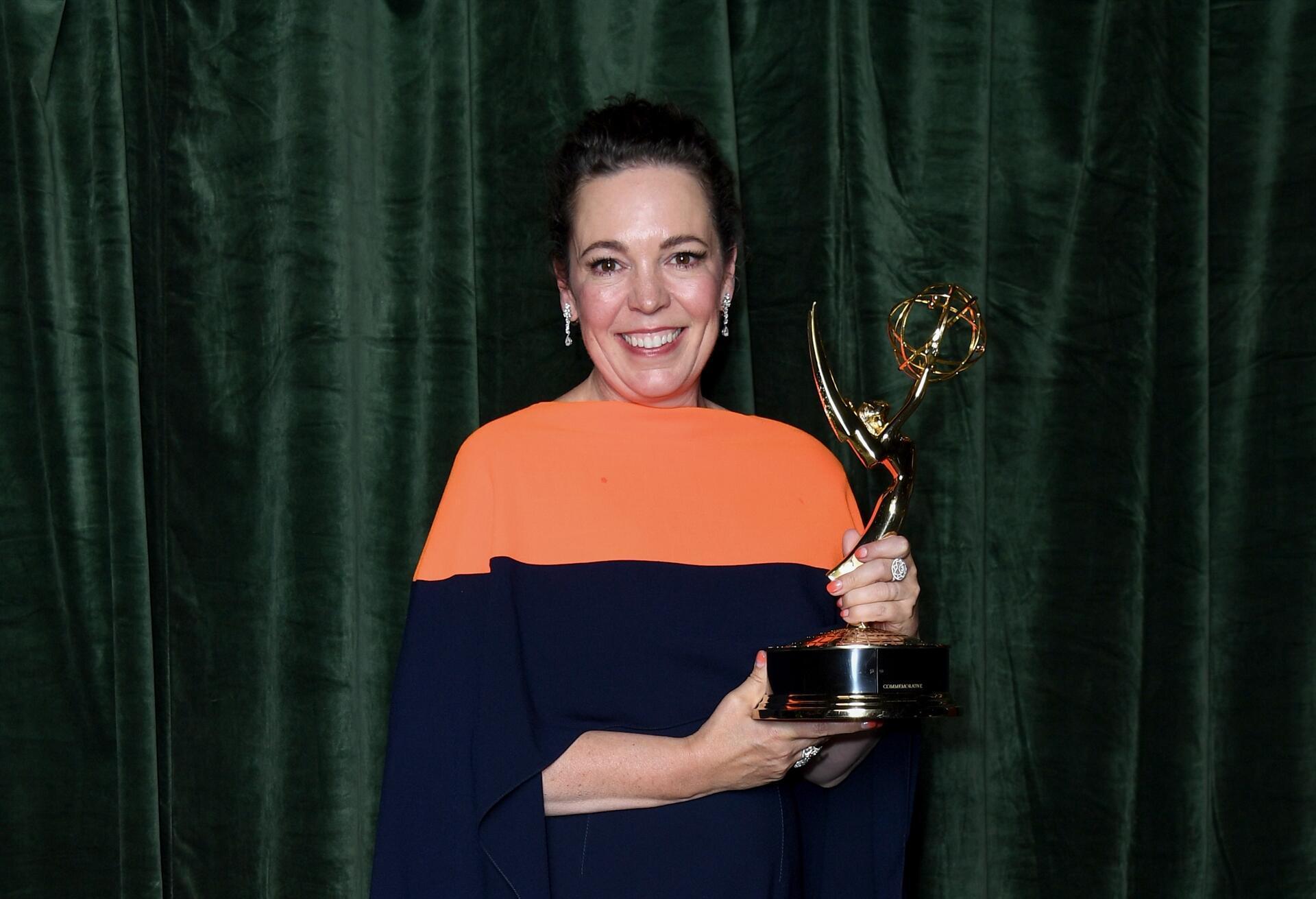 Foto de Olivia Colman. A mulher branca de cabelo preto preso em um coque sorri segurando uma estatueta na sua direita. Ela veste uma blusa laranja com azul e brincos pratas. O fundo é um pano verde.