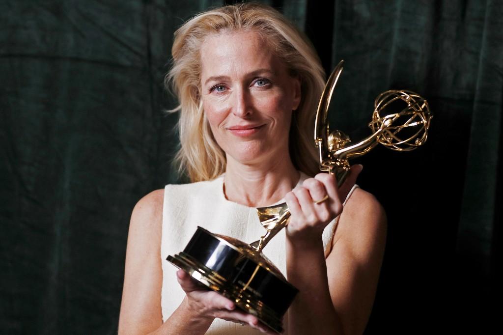 Foto de Gillian Anderson. A mulher branca, que tem cabelo loiro e curto, usa um vestido branco. segura na sua frente uma estatueta do Emmy, mostrando para a câmera. A mulher sorri. O fundo é um pano verde.
