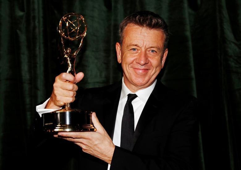 Foto de Peter Morgan. O homem branco segura sua estatueta com as duas mãos, sorrindo para camera. Seu cabelo é curto e ele veste terno e gravata pretas por cima de uma blusa branca. O fundo é um pano verde.