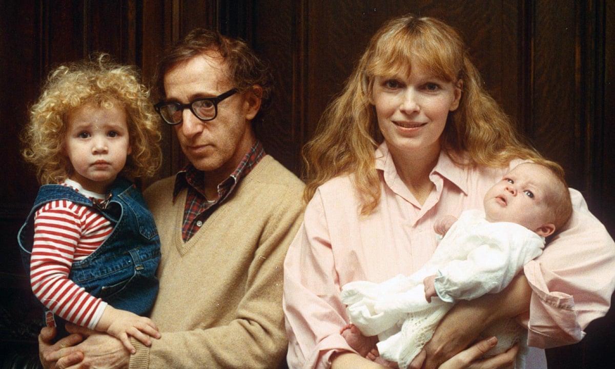 A imagem é uma foto de Woody Allen e Mia Farrow segurando no colo, respectivamente, Dylan e Ronan Farrow.